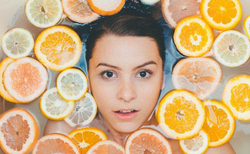 chica rodeada de naranjas